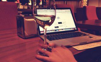 dame werkt op laptop met glas wijn erbij